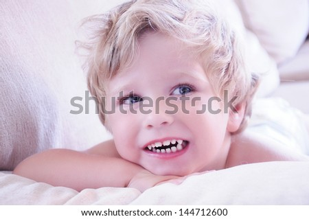 Cute Little Boy Lying In The Sofa At Home. - stock photo