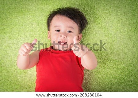 cute little boy lying on a green lawn and thumbs up - stock photo