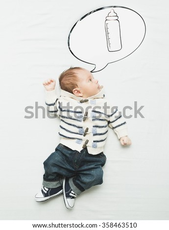 Cute little boy lying on bed and dreaming of bottle with milk - stock photo