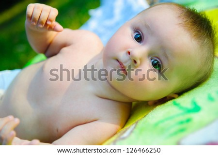 Cute little boy lying outdoors in the park - stock photo