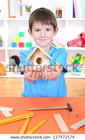 Cute little boy makes birdhouse for birds