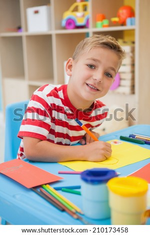 Cute little boy making art in classroom at the nursery school - stock photo
