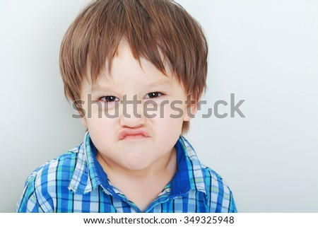 Cute little boy making funny faces pretend he is angry - stock photo