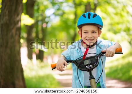 Cute little boy on bike in forest - stock photo