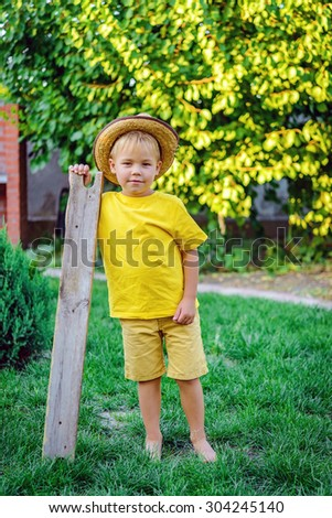 Cute little boy on the green grass in a cowboy hat with wooden board