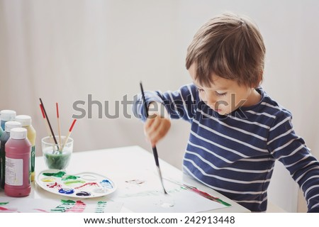Cute little boy painting at home, concentrated - stock photo