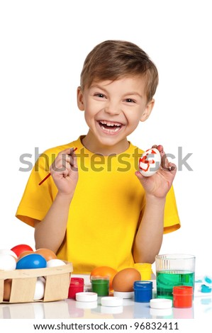 Cute little boy painting Easter eggs isolated on white background - stock photo