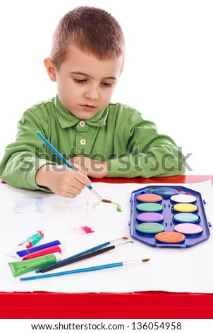 Cute little boy painting with brush isolated on white background
