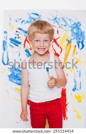 Cute little boy painting with brush. School. Preschool. Education. Creativity. Studio portrait over white background - stock photo
