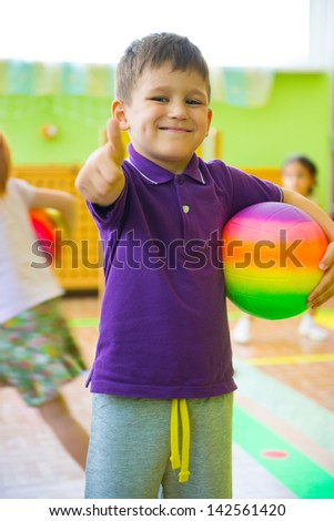 Cute little boy playing at daycare gym with ball - stock photo