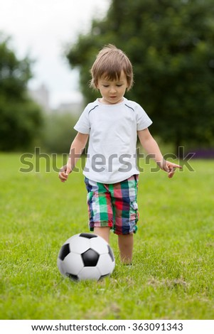 Cute little boy, playing football in the park, summertime