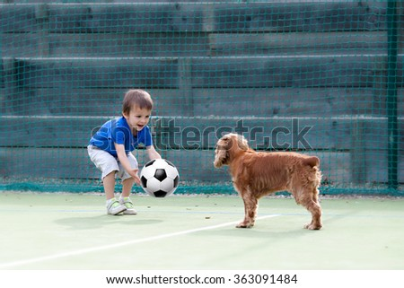 Cute little boy, playing football with his dog on the playground - stock photo
