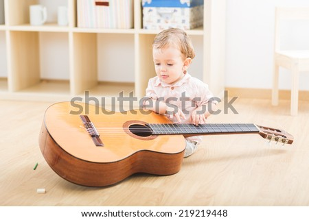 Cute little boy playing guitar at the nursery school - stock photo