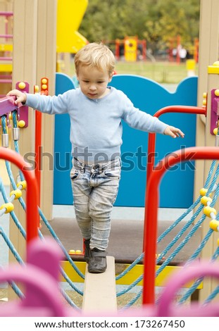 Cute little boy playing in a playground carefully balancing on a plank suspended by ropes with colourful guide rails to hold onto - stock photo