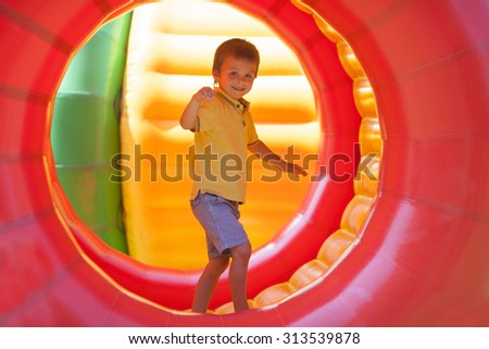 Cute little boy, playing in a rolling plastic cylinder ring, full with air, outdoor - stock photo