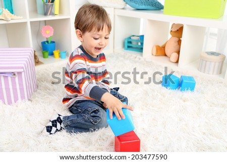 Cute little boy playing in room - stock photo