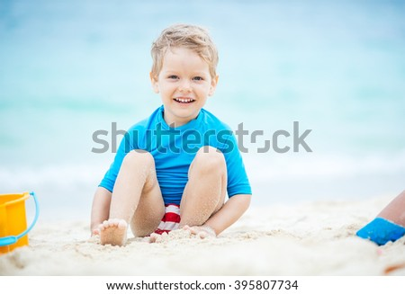 Cute little boy playing on the beach - stock photo