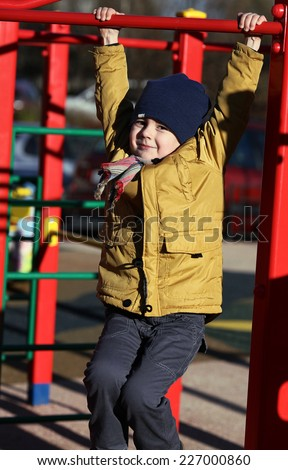 cute little boy playing on the playground, autumn time - stock photo