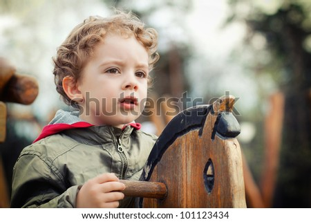cute little boy playing on the playground outdoor - stock photo