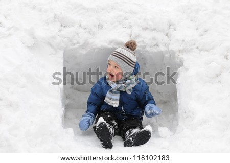 Cute little boy playing outdoors in the snow