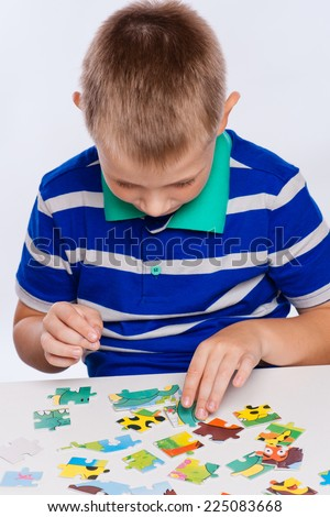 Cute little boy playing puzzles at the table - stock photo