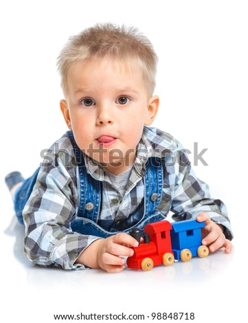 Cute little boy playing toy trains. In the studio.