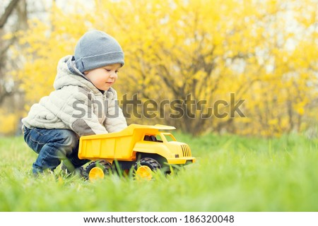 cute little boy playing with a car in the park - stock photo