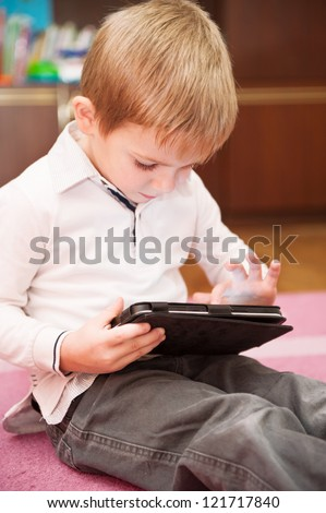 Cute little boy playing with digital tablet computer