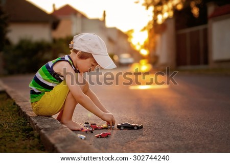 Cute little boy, playing with little toy cars on the street on sunset, summertime - stock photo