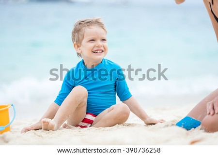 Cute little boy playing with mother on the beach