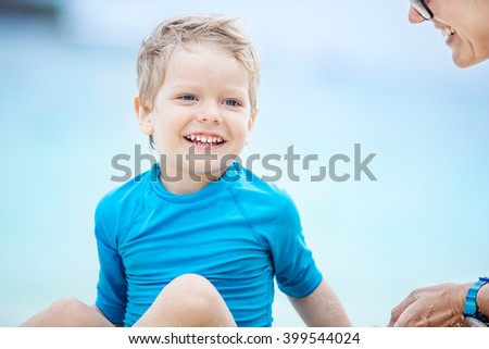 Cute little boy playing with mother on the beach - stock photo
