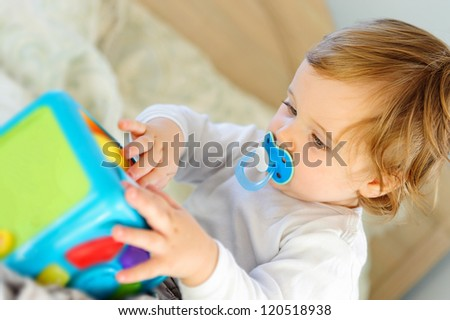 Cute little boy playing with toy at home