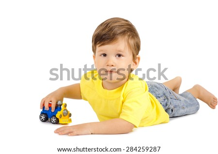 Cute little boy playing with toy car on floor isolated on white background