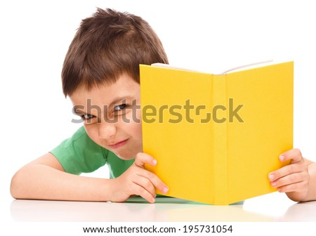 Cute little boy plays with book while sitting at table, isolated over white - stock photo