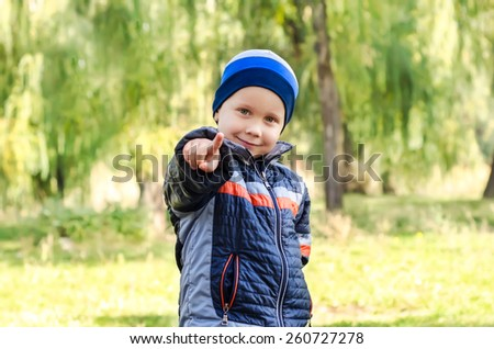 Cute little boy pointing forward in autumn park - stock photo