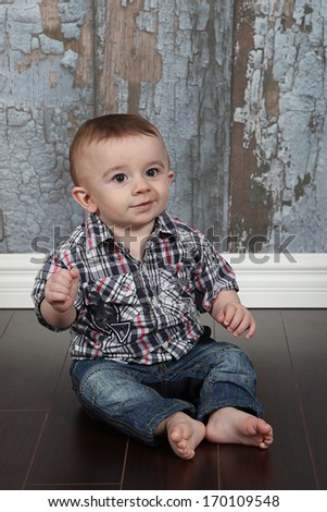 Cute little boy posing for camera on white background