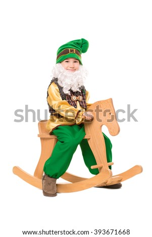 Cute little boy posing in a gnome costume sitting on the rocking horse. Isolated - stock photo