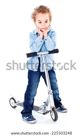 Cute little boy posing with his scooter - stock photo