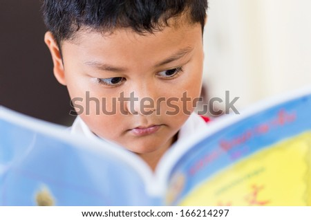 cute little boy reading at the table