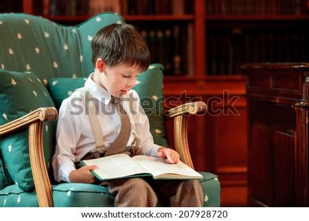 Cute little boy reading book on armchair - stock photo