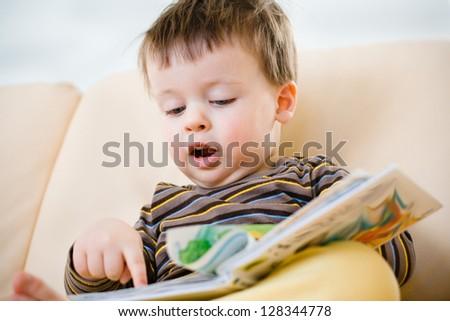 Cute little boy reading book on sofa - stock photo