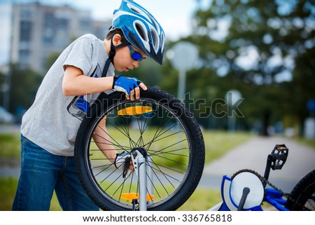 Cute little boy repairing bicycle outdoors at summer - stock photo
