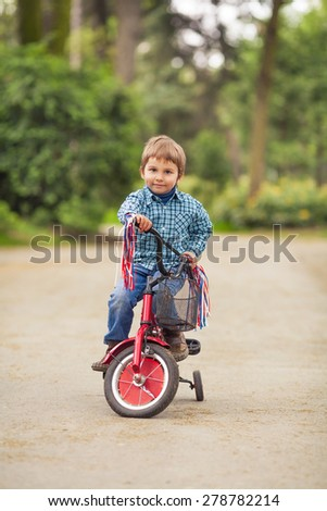 Cute little boy riding a bike in a park - stock photo