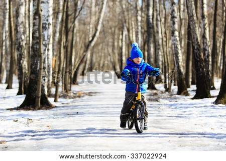 cute little boy riding bike in winter, kids sport - stock photo