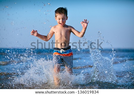 Cute little boy running through the water at the beach - stock photo