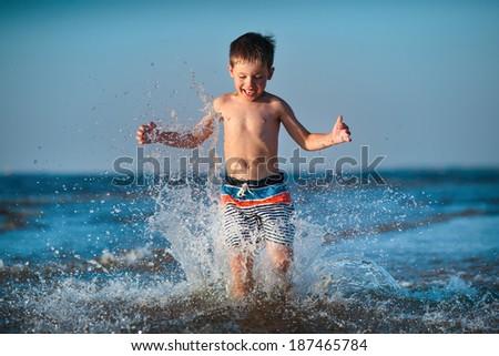 Cute little boy running through water at the beach - stock photo