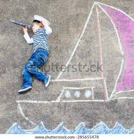 Cute little boy sailing on ship or boat picture drawing with chalk. Creative leisure for children outdoors in summer - stock photo