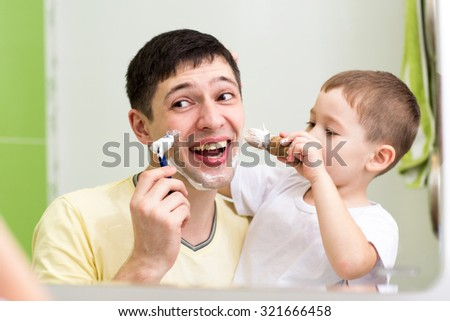 cute little boy shaving his father at mirror in bathroom  - stock photo