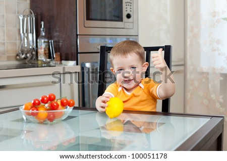 cute little boy sitting at kitchen with healthy food and showing thumb up