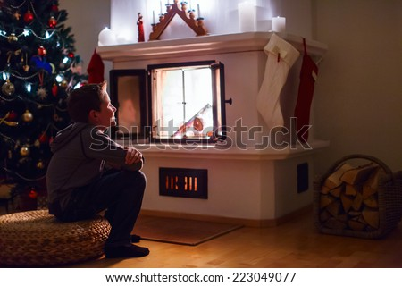 Cute little boy sitting by a fireplace at home on Christmas eve